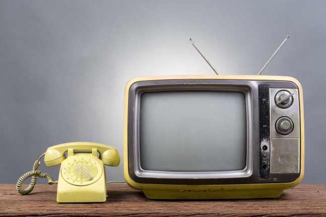 Vintage Television with old telephone on wood table