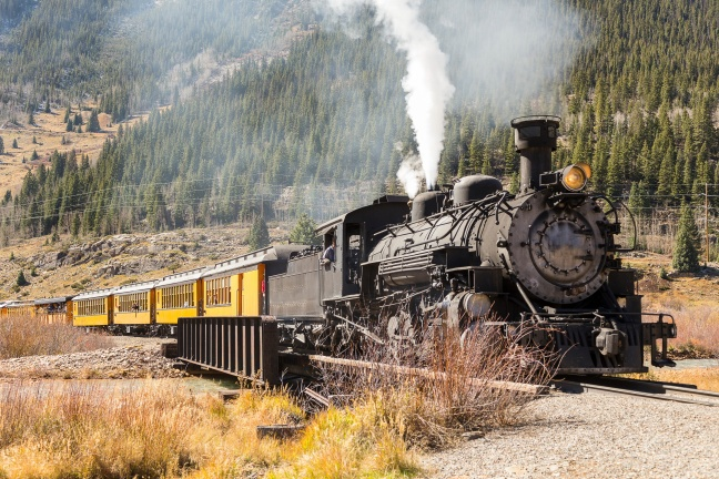 Vintage steam train with yellow wagons going uphill in mountain area