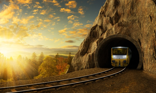 Mountain railroad with train in tunnel in rock above landscape.