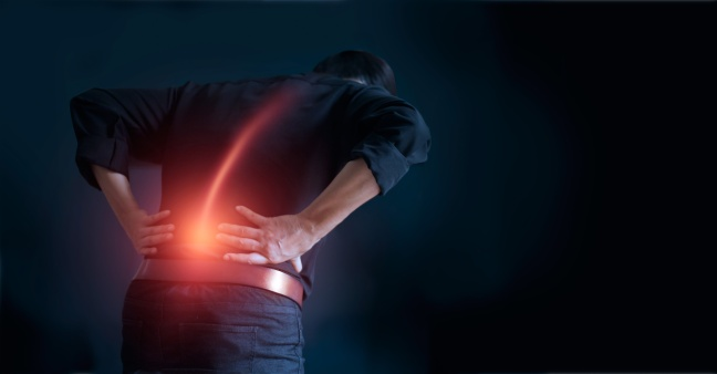Man suffering from back pain cause of office syndrome, his hands touching on lower back. Medical and heathcare concept.