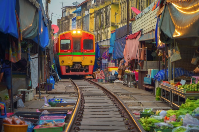Rom Hoop market. Thai Railway with a local train run through Mae Klong Market in Samut Songkhram Province, Thailand. Tourist attraction in travel and transportation concept.