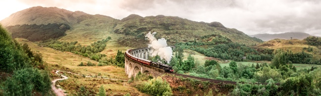 Glenfinnan Railway Viaduct with Jacobite steam train passing over. Harry Potter famous Glenfinnan viaduct, Scotland in cloudy weather with steam train.